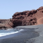 El Golfo - above on the rocks is the main viewpoint of Charco de los Clicos. View from the beach near the lake.